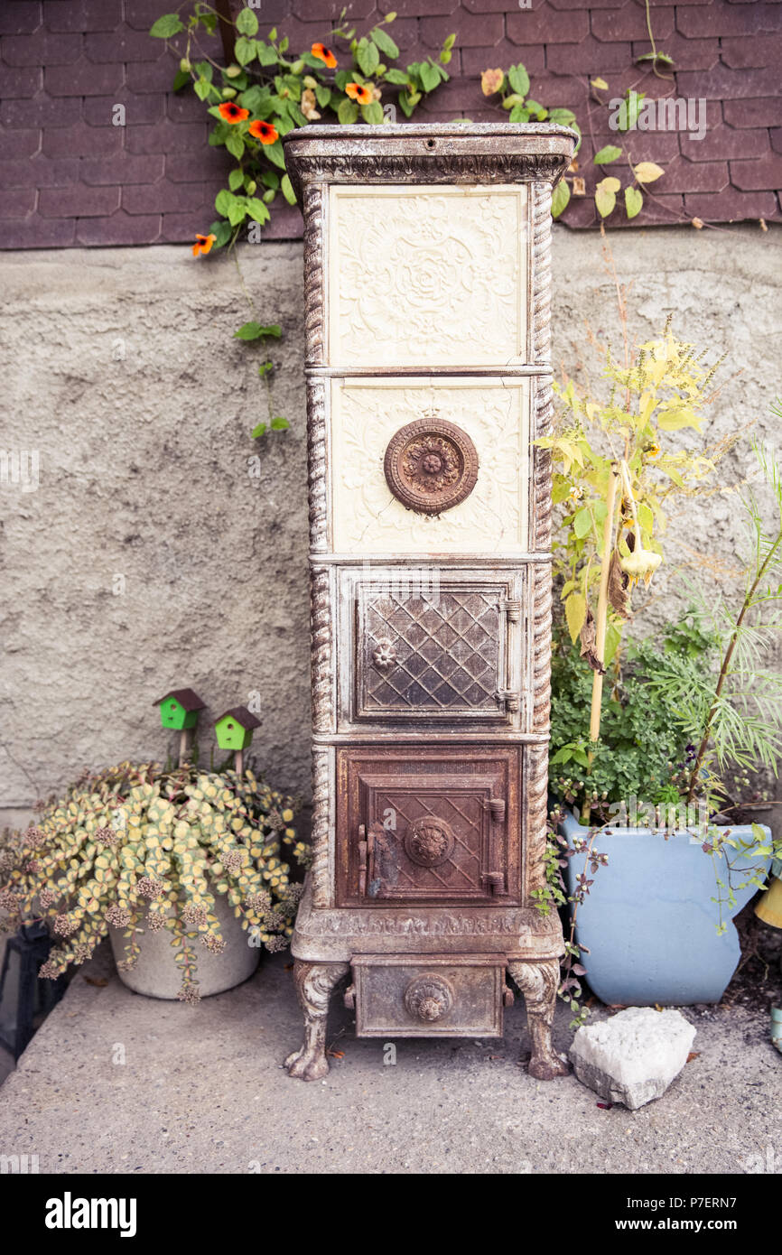 Cracked Vintage Cast Iron Stove Outdoors Home Decoration - Stock Image
