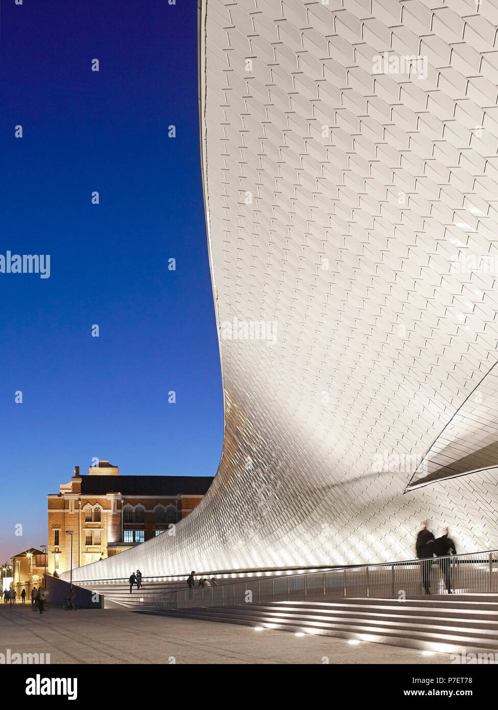 Illuminated and glowing facade at night. MAAT, Lisbon, Portugal. Architect: A_LA, 2016. - Stock Image