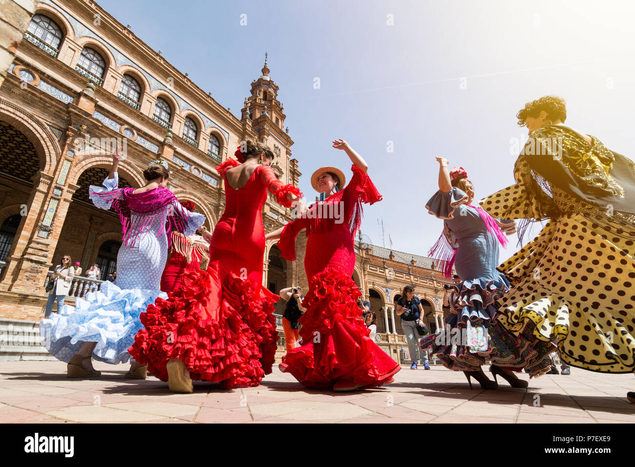SEVILLE, SPAIN - MAY 2017: Young women dance flamenco on Plaza de Espana during famous Feria festival - Stock Image