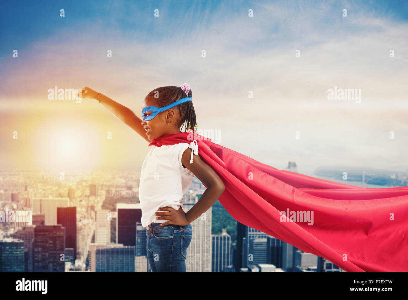 Child acts like a superhero to save the world - Stock Image