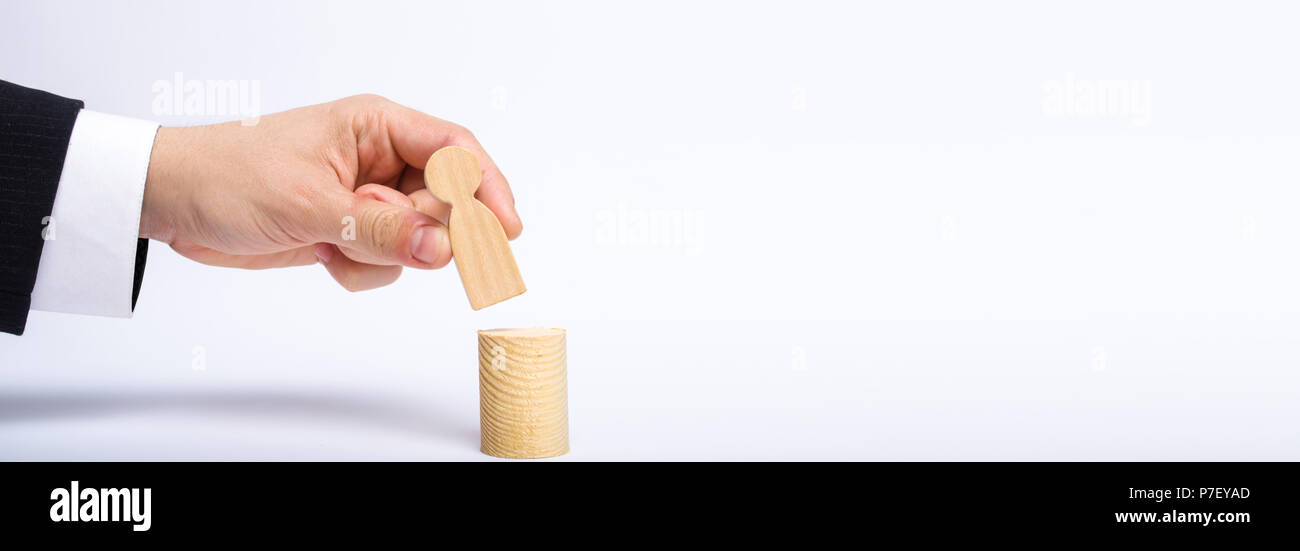 A man's hand puts a person's figure on top of his new post. A businessman appoints a person to a managerial position. Recruitment and leadership posit - Stock Image