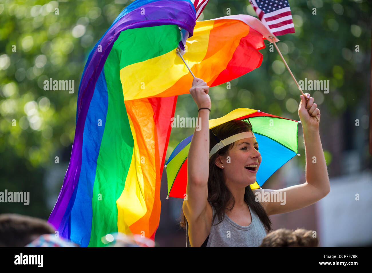 NEW YORK CITY - JUNE 25, 2017: Woman waves rainbow and US flags on the sidelines of the annual Pride Parade as it passes through Greenwich Village. - Stock Image