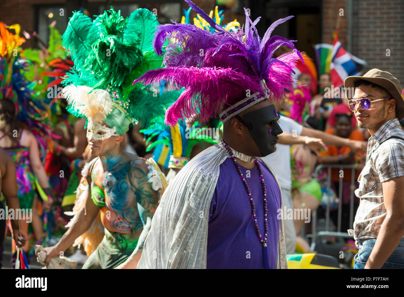 NEW YORK CITY - JUNE 25, 2017: Participants dressed in flamboyant feathery carnival costumes in the annual Pride Parade as it passes through Greenwich - Stock Image