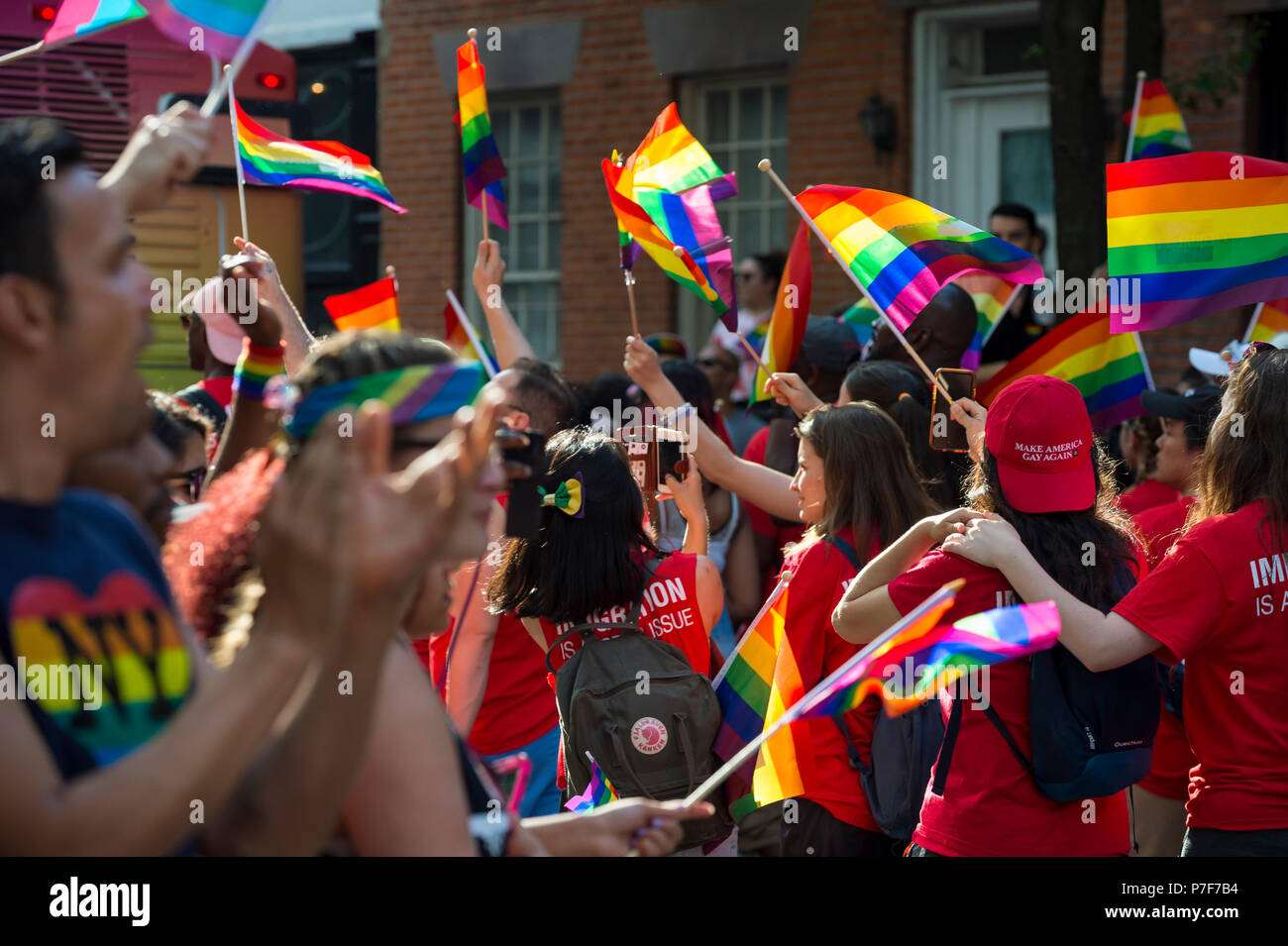 NEW YORK CITY - JUNE 25, 2017: Supporters wave rainbows flags on the sidelines of the annual Pride Parade as it passes through Greenwich Village. - Stock Image