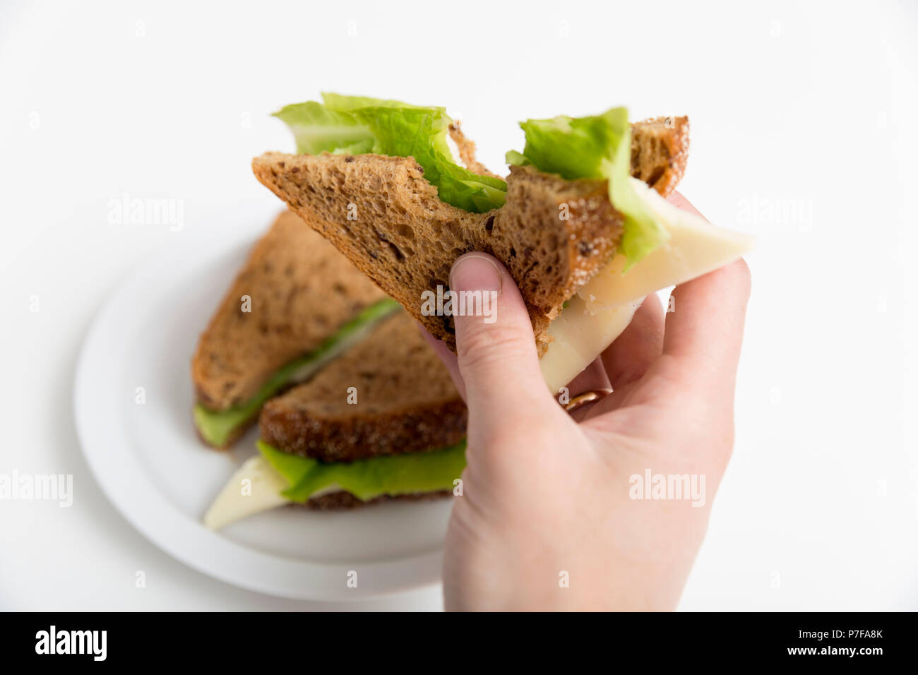 Bitten Cheese And Lettuce Sandwich In Hand Whole Sandwich On White Plate Lunch Break Healthy Snack Concept Stock Photo Alamy