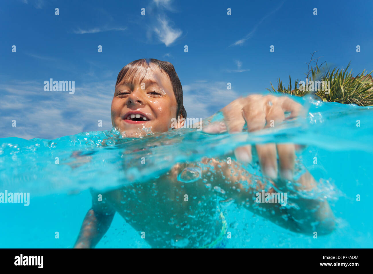 Happy preteen boy swimming in outdoor pool - Stock Image