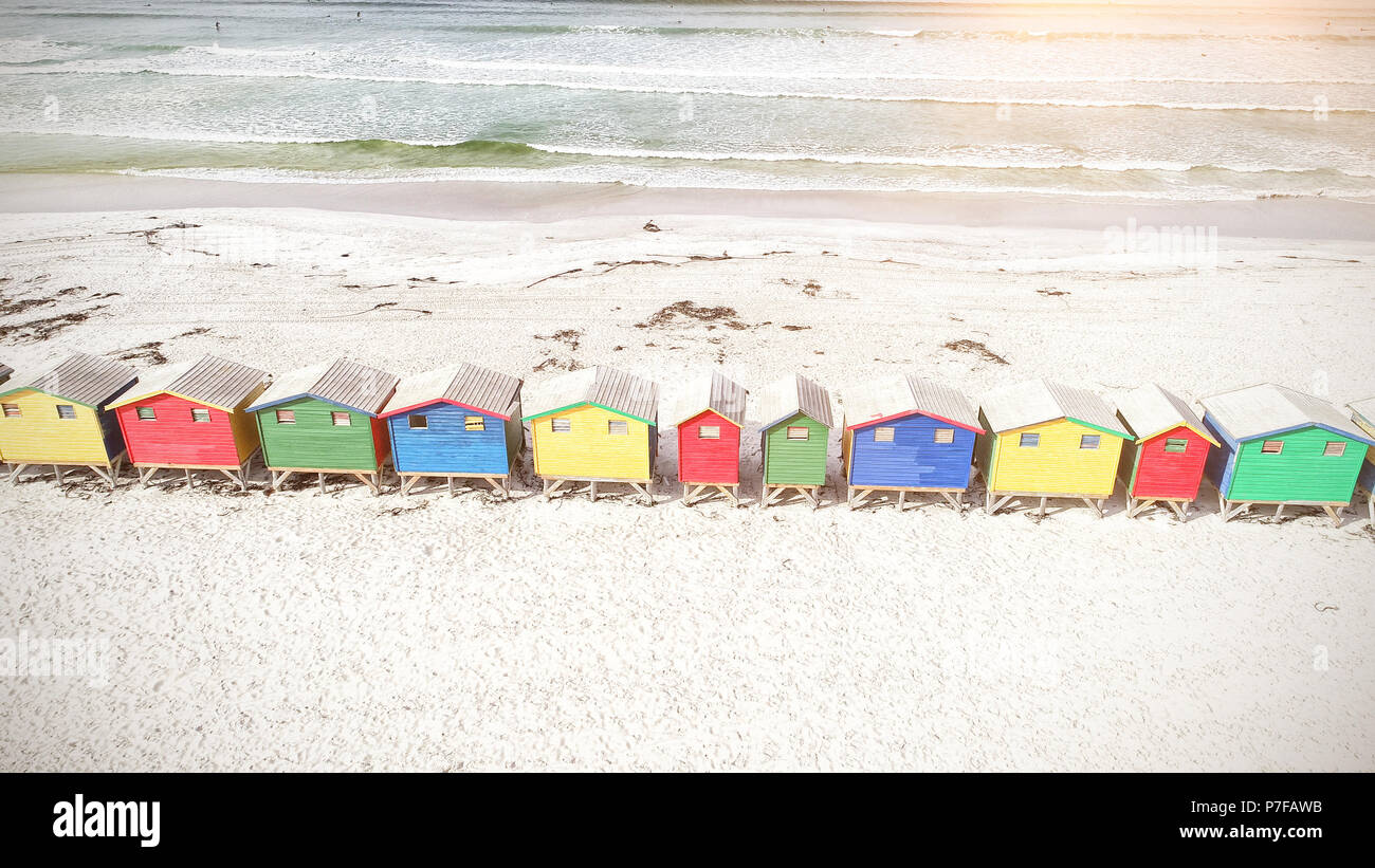 Colorful wooden houses on sand - Stock Image