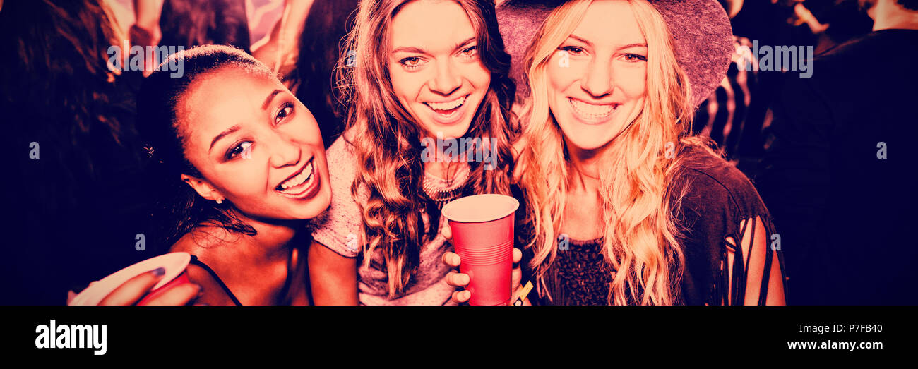 Female friends with disposable cups in club - Stock Image