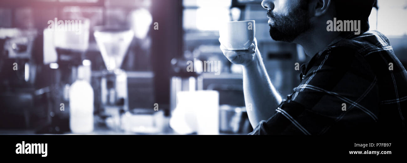 Side view of man drinking coffee - Stock Image