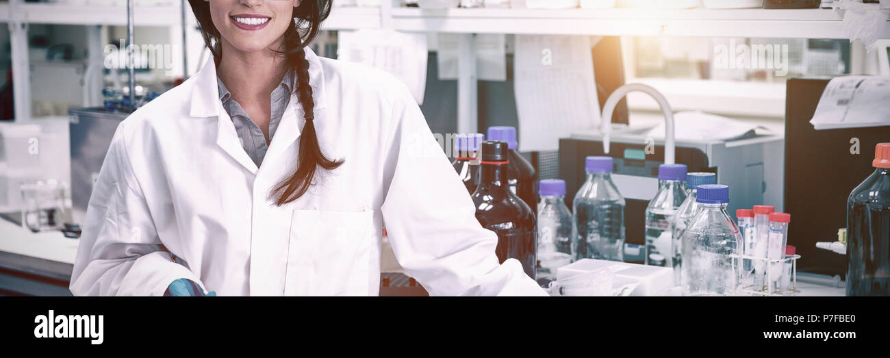 Portrait of a smiling chemist leaning against desk - Stock Image