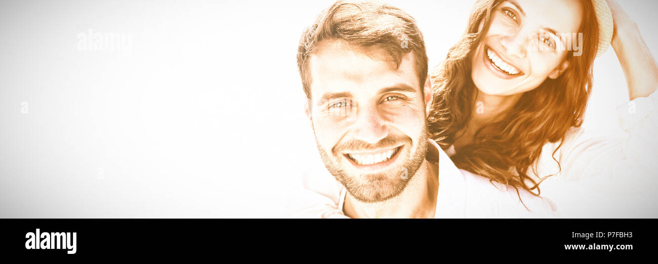 Man doing piggy-back to girlfriend - Stock Image