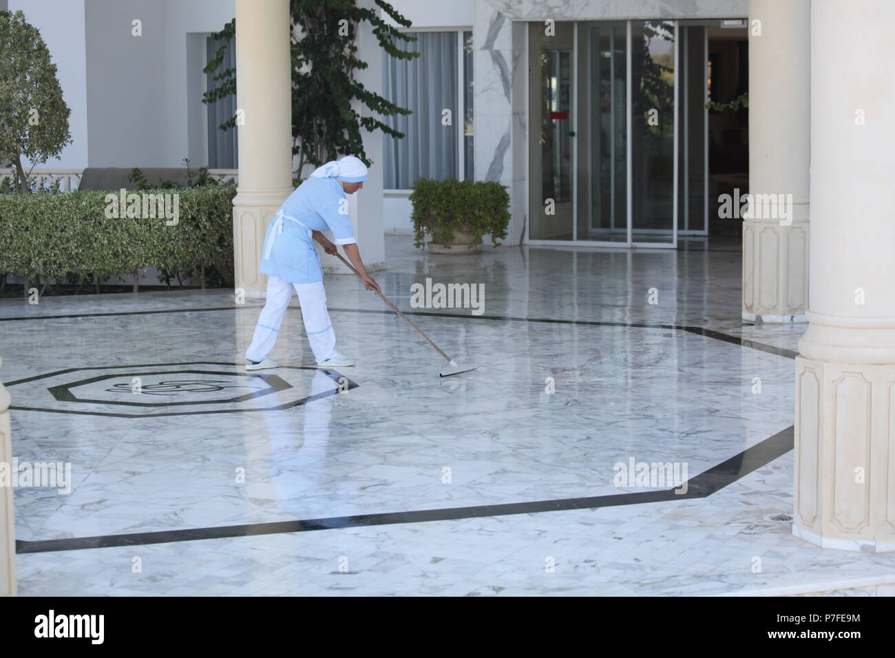 Dressed in clean uniform local cleaning lady is tidying up marble floor at the entrance of the 4* hotel in Hammamet, big tourist center in Tunisia - Stock Image