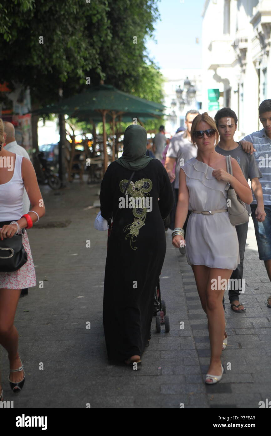 Muslim lady walking down the street in traditional dress in down town Tunis as tourist visitors girls walking in mini-skirts and with open shoulders - Stock Image