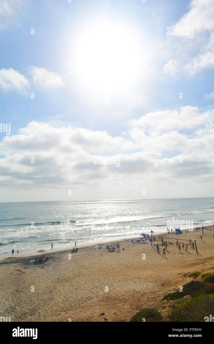 Bright California beach summer with people playing in the sand and a sun with clouds - Stock Image