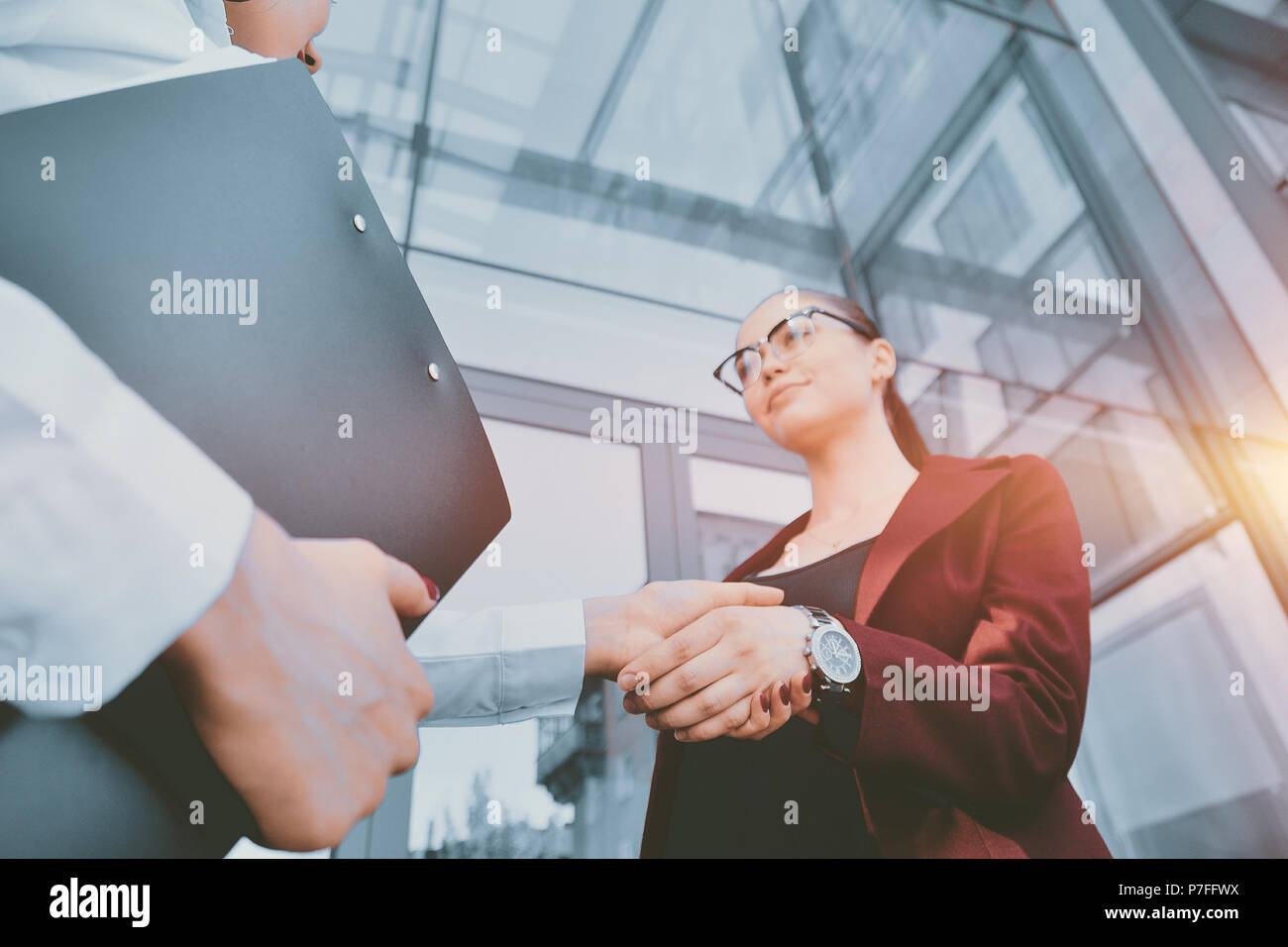 Handshake of two young girls against the background of a multi-storey office building. Make a deal. Friendly relations. Office staff. - Stock Image