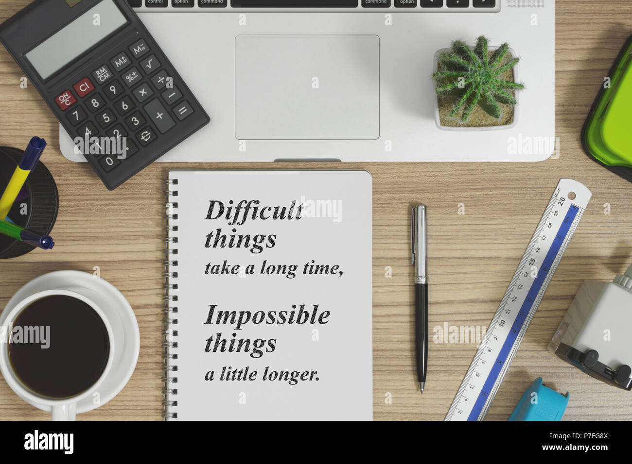 Office supplies on wood office desk. Notebook with motivational and inspirational quote. - Stock Image