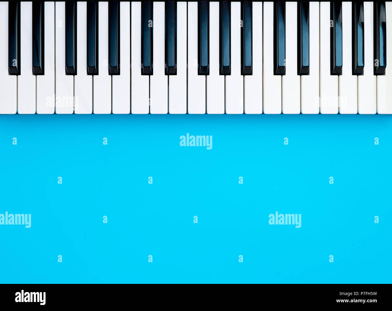 Music Synthesizer Piano Keyboard keys on blue copy space - Stock Image