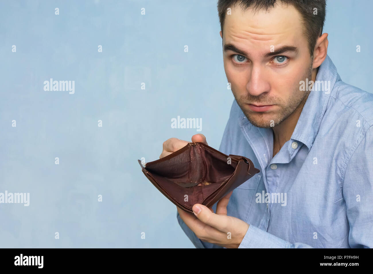 Bankruptcy - Business Person holding an empty wallet. Man showing empty wallet by showing the inconsistency and lack of money and not able to pay the  Stock Photo