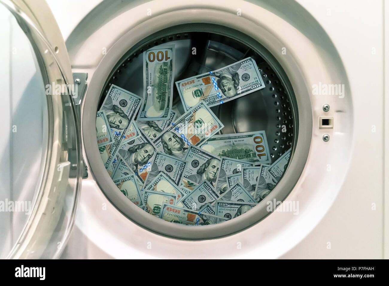 Close-up Of Pile Of Dirty Money Placed In Washing Machine. concept of laundering illegal money. launder money. black market - Stock Image