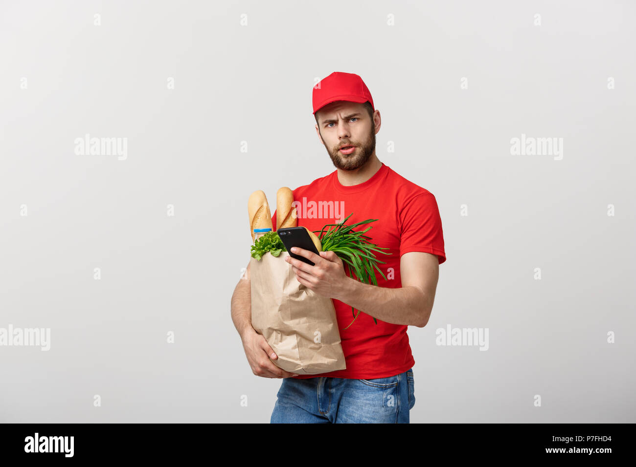 Delivery man holding paper bag with food and shock or angry with something in mobile phone on white background Stock Photo