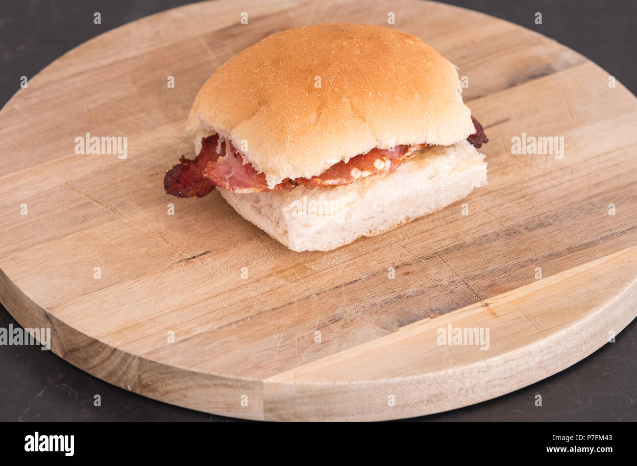 A scottish roll and bacon on a wooden board. A good image for a baker food retailer. - Stock Image