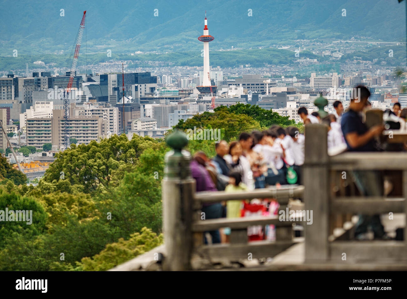 Long shot of Kyoto city with blurred tourists visiting temple in the foreground, focus on background Stock Photo