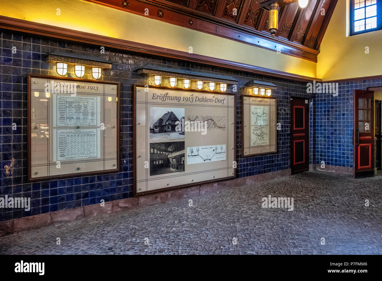 Berlin Dahlem-Dorf U-Bahn underground railway station on U 3 line. Historic building interior with blue tiles, wood panel ceiling, Information boards - Stock Image
