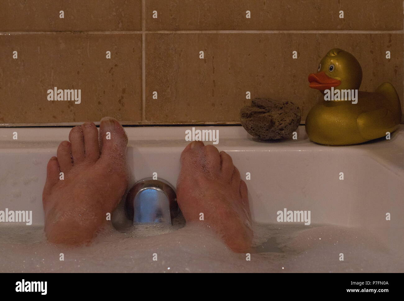 Feet in a foam bath with bubbles and a toy duck image with copy ...