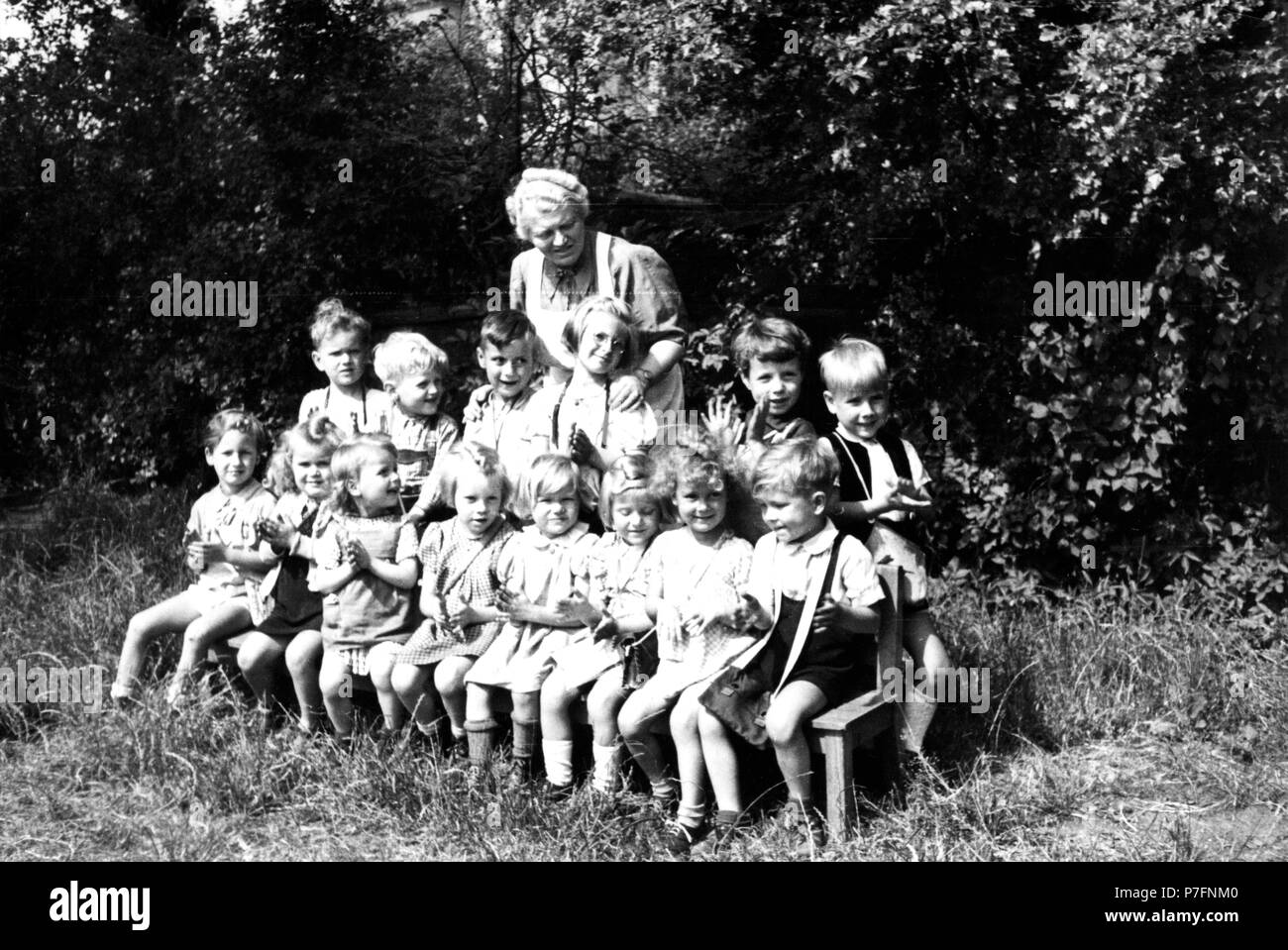 Children can be photographed in the green with the kindergarten teacher, ca. 1955, Leipzig, Germany - Stock Image