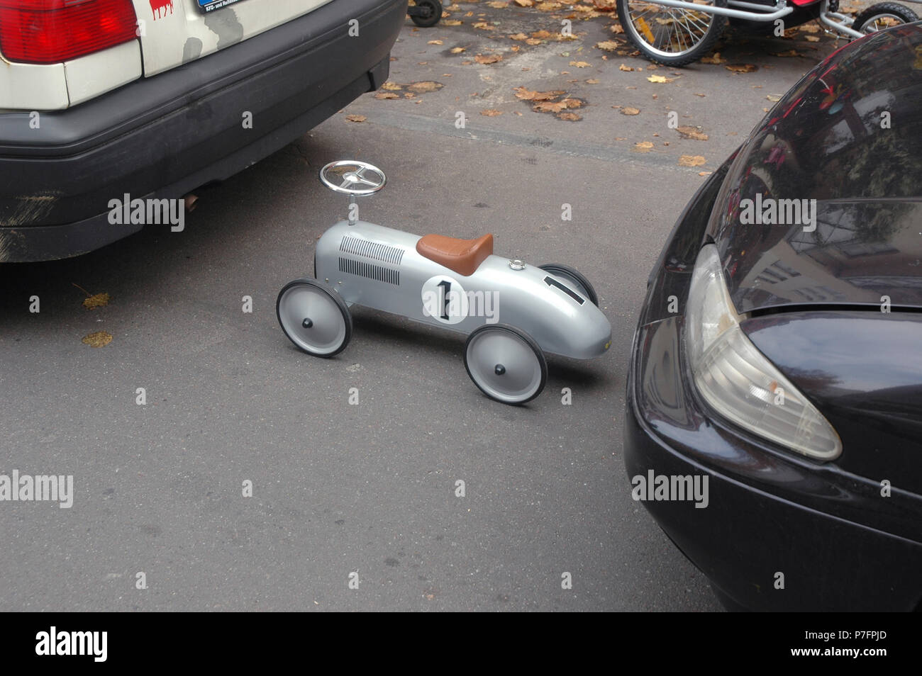 Size difference, small toy car on the parking lot, Berlin, Germany - Stock Image