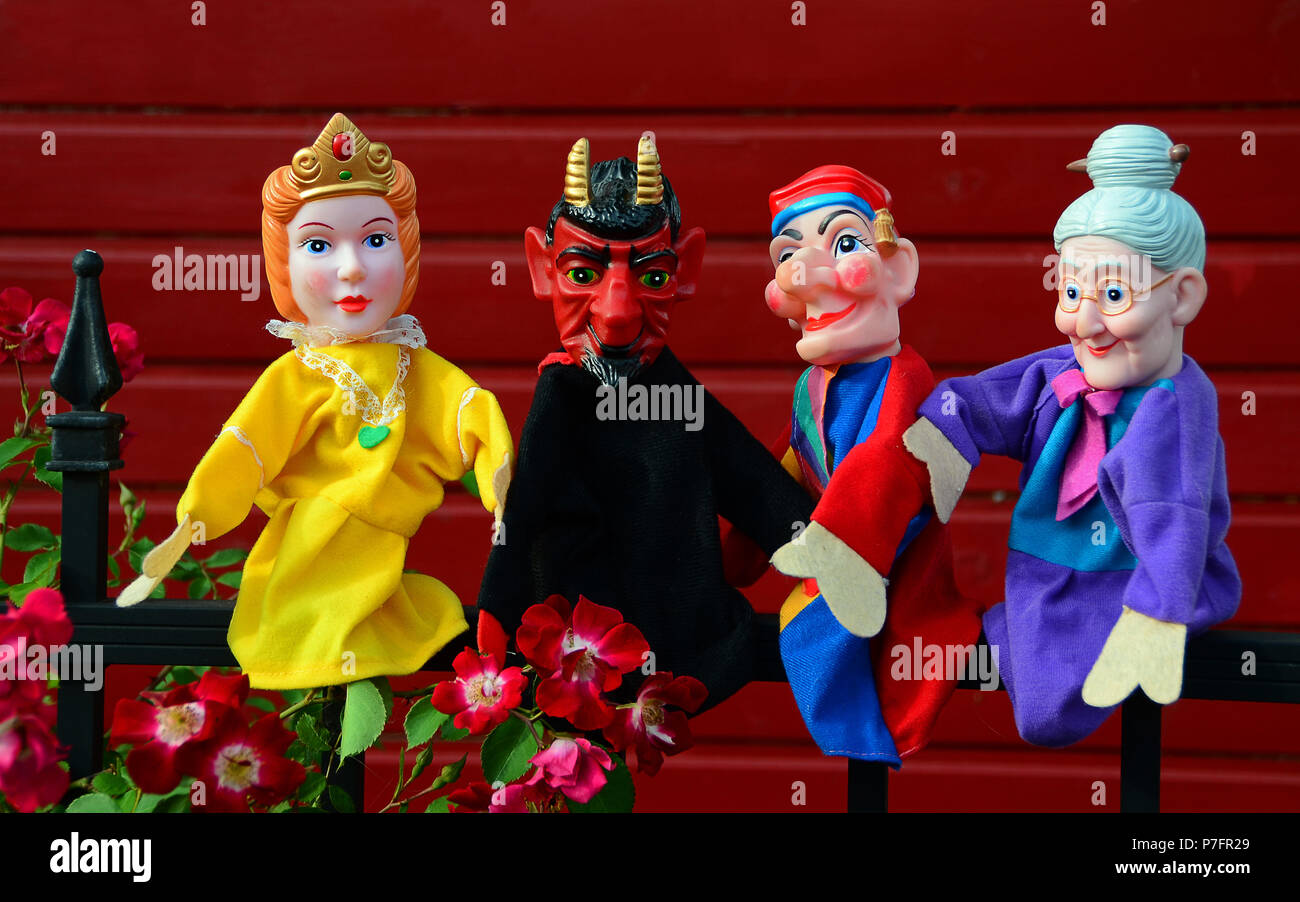 Punch puppets, Punch, Princess, Grandmother and Devil sitting on a metal fence - Stock Image