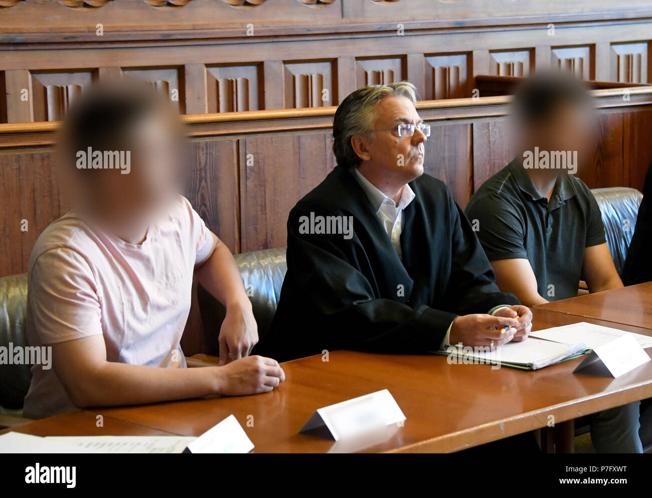 Flensburg, Germany. 06th July, 2018. The two defendants (L and R) indicted for murder standing in the dock with their lawyer Martin Unger. The district court is pronouncing their verdict in the murder trial against the two 20-year-olds, who woke up a coeval in the night before Easter Sunday 2017 and stabbed him by the front door. Credit: Carsten Rehder/dpa/Alamy Live News - Stock Image
