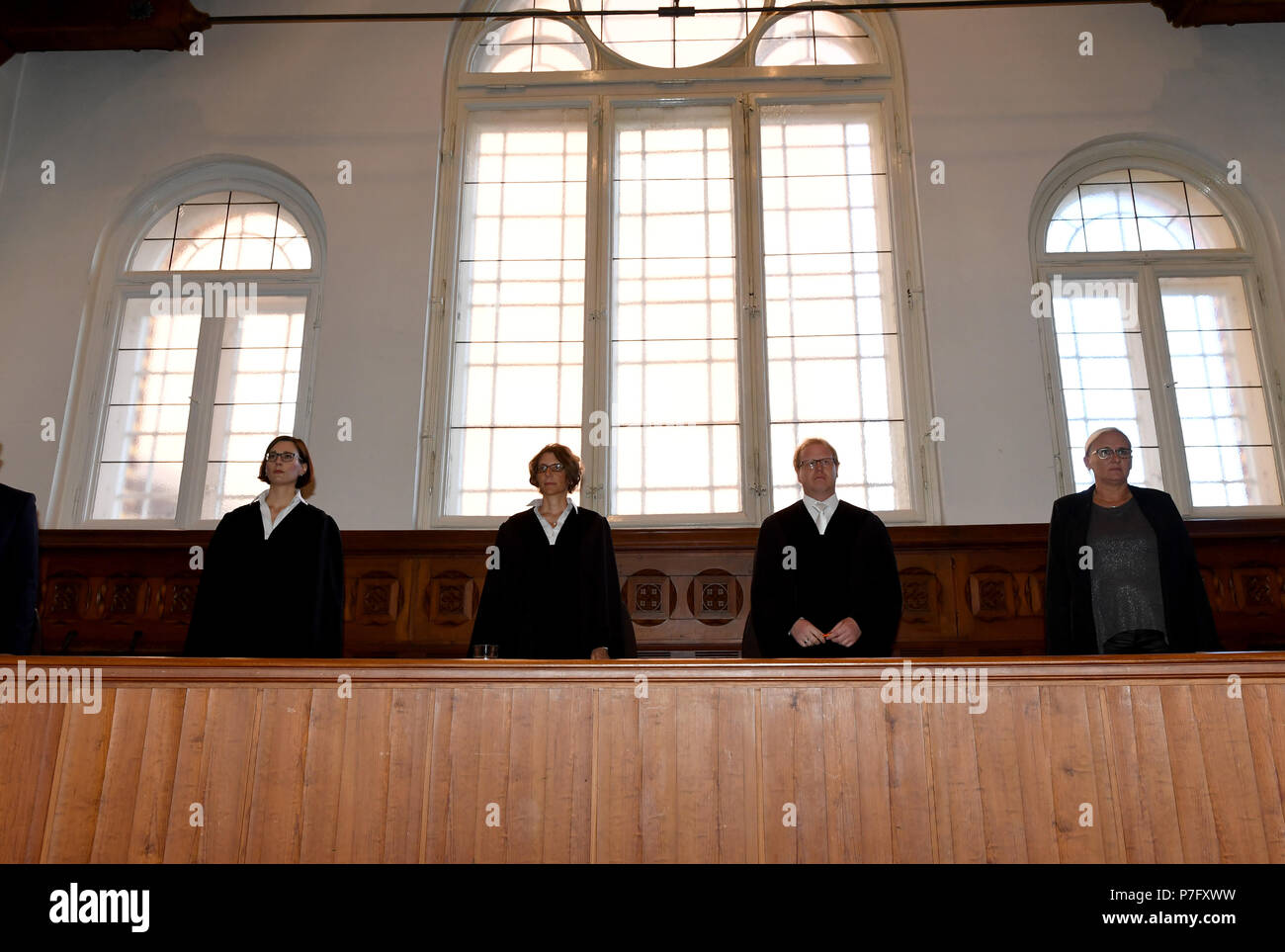 Flensburg, Germany. 06th July, 2018. The judges in the trial against two defendants indicted for murder standing in front of windows by their bench. The district court is pronouncing their verdict in the murder trial against the two 20-year-olds, who woke up a coeval in the night before Easter Sunday 2017 and stabbed him by the front door. Credit: Carsten Rehder/dpa/Alamy Live News - Stock Image