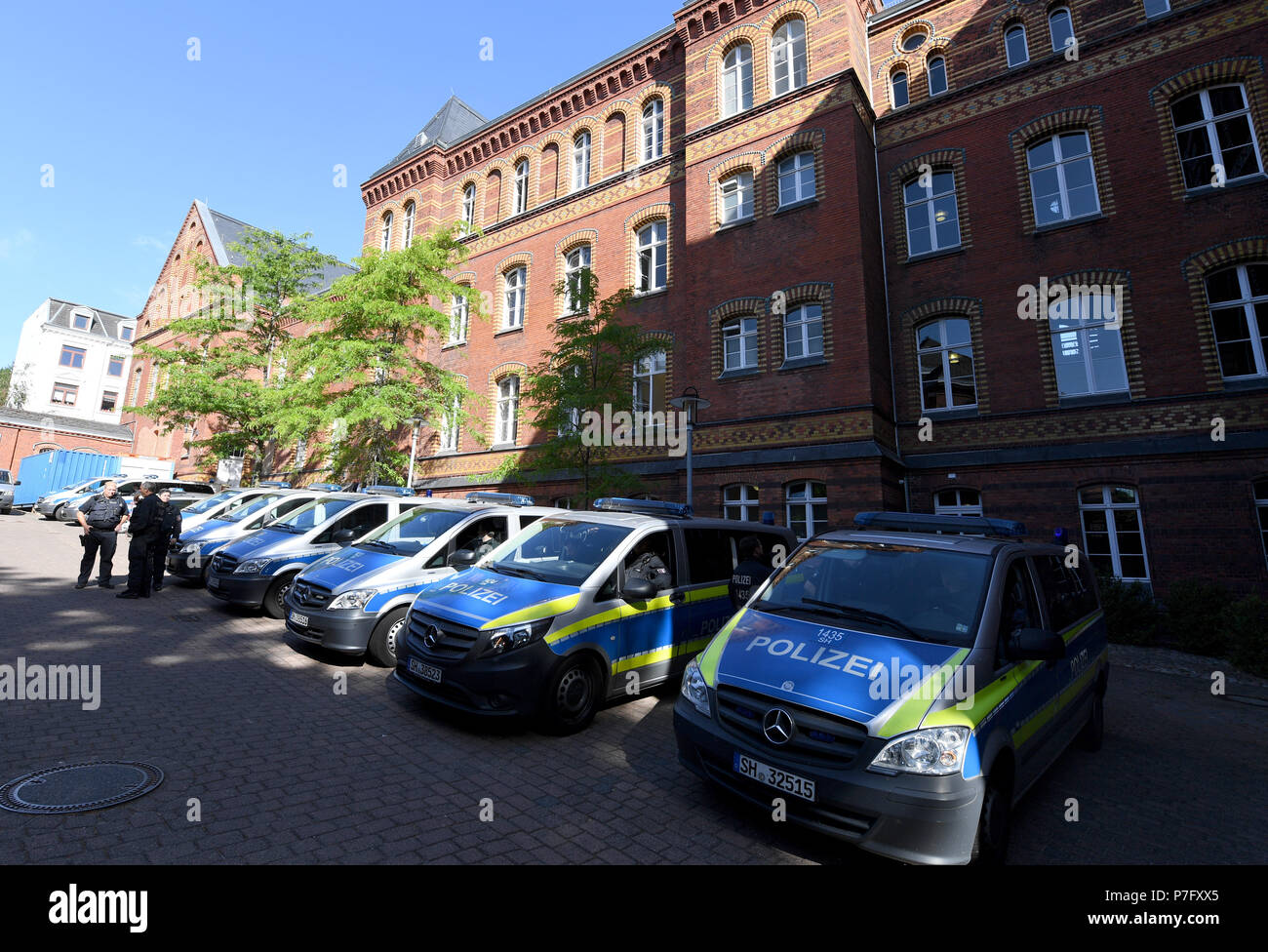 Flensburg, Germany. 06th July, 2018. Police vehicles standing in front of the district court before a murder trial. The district court is pronouncing their verdict in the murder trial against the two 20-year-olds, who woke up a coeval in the night before Easter Sunday 2017 and stabbed him by the front door. Credit: Carsten Rehder/dpa/Alamy Live News - Stock Image