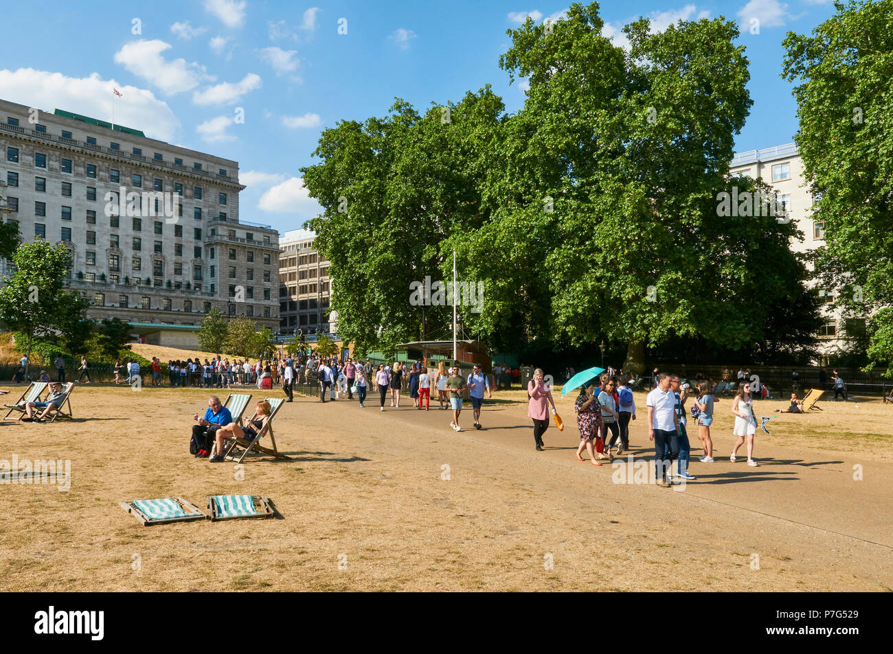 Tourists arriving from Green Park Underground station, walking through a scorched Green Park, London UK, during the July 2018 heatwave - Stock Image