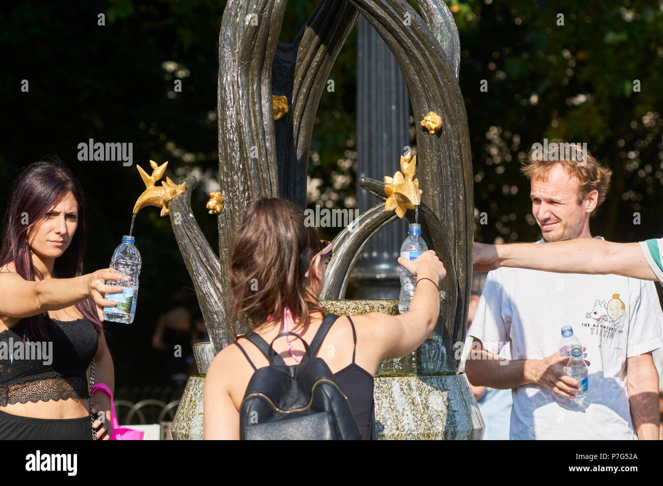 Tourists filling water bottles from the drinking fountain outside Green Park Tube station, London UK,  during the July 2018 heatwave, with temperatures of around 30 degrees - Stock Image