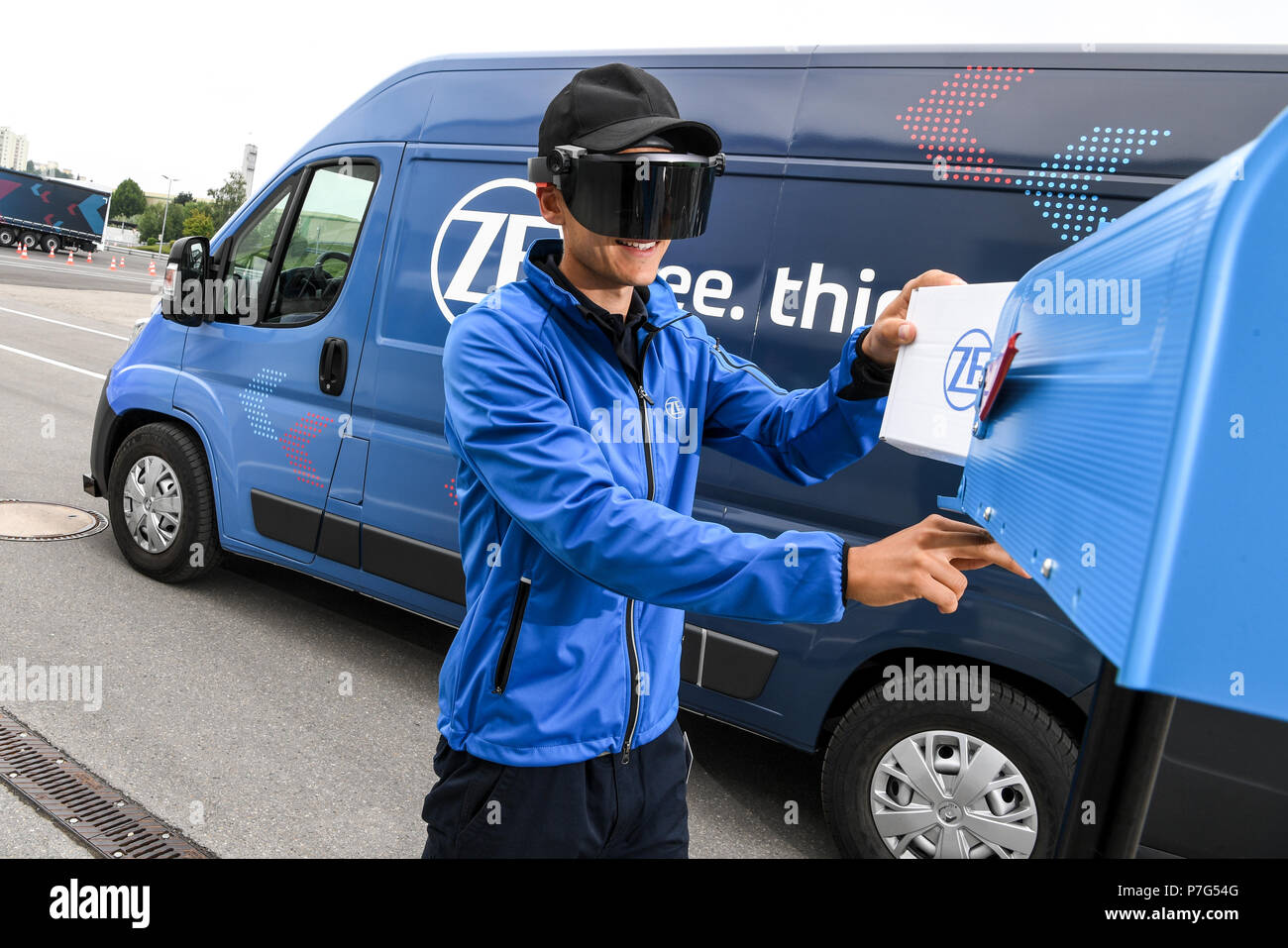 27 June 2018, Friedrichshafen, Germany: A ZF employee carries a package while the ZF Innovation Van drives on by itself, for example to move out of a no-parking zone. A pair of data glasses provides delivery personnel with information on the next stop. Photo: Felix Kästle/dpa Stock Photo