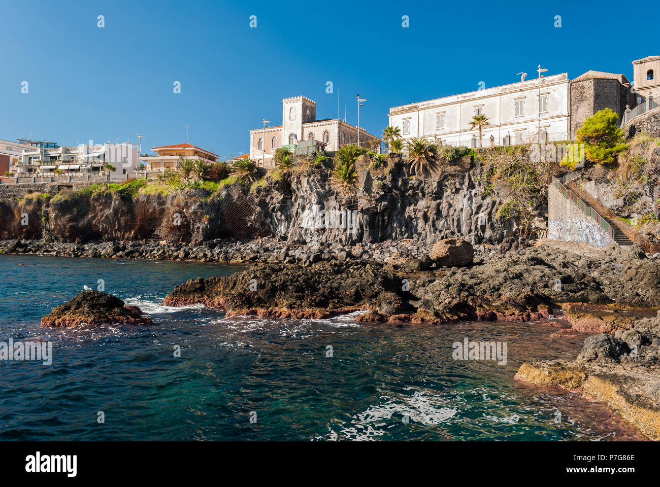 Rocky coastline with typical pillows lava in the town of Aci Castello, in Sicily - Stock Image