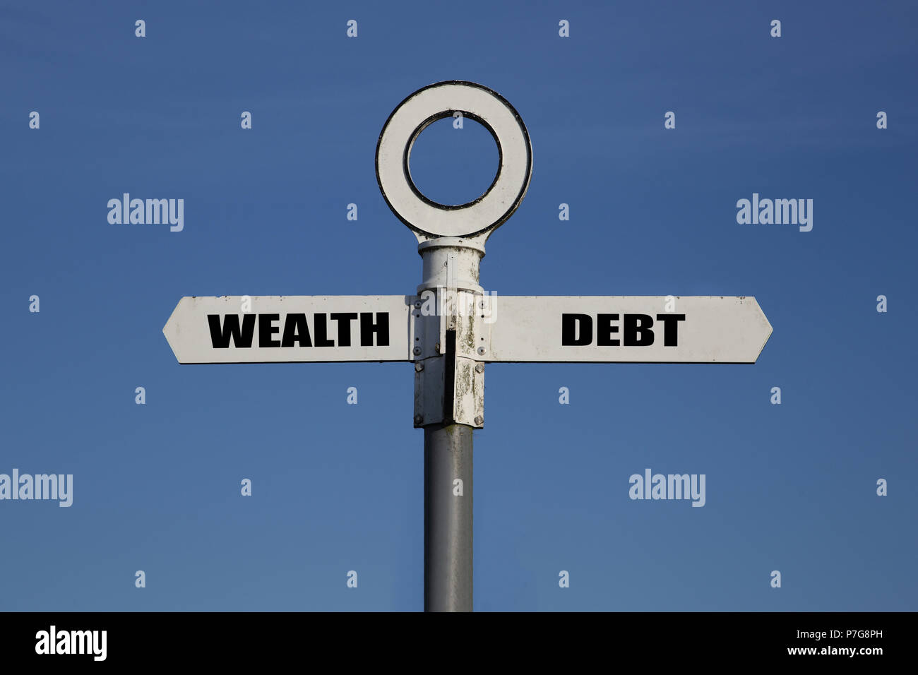 Old road sign with wealth and debt pointing in opposite directions against a blue sky - Stock Image