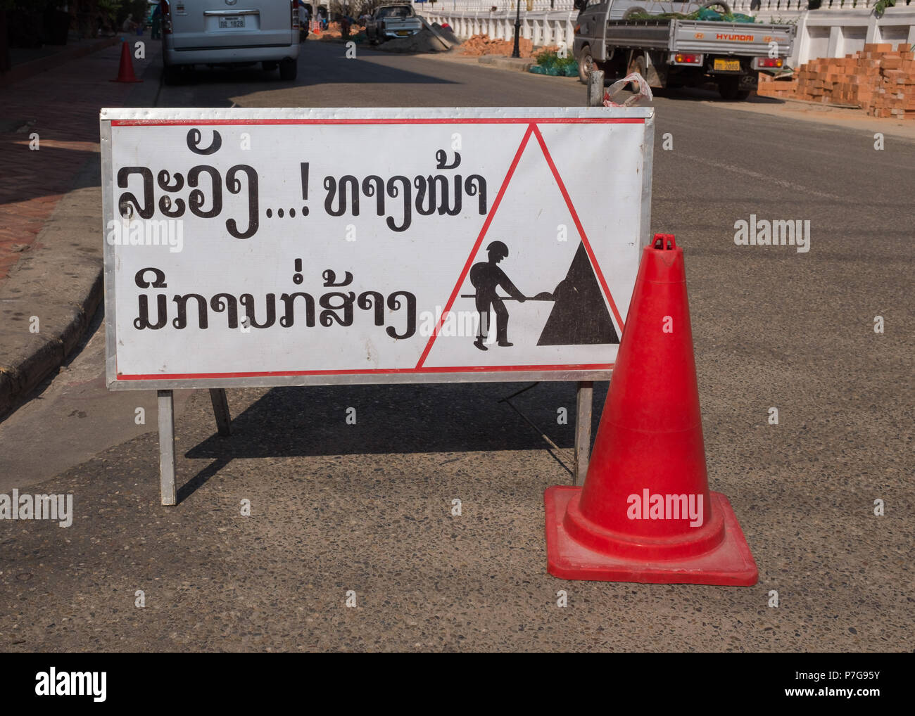 Men at work road sign with traffic cone in Vientiane, Laos, Asia. - Stock Image