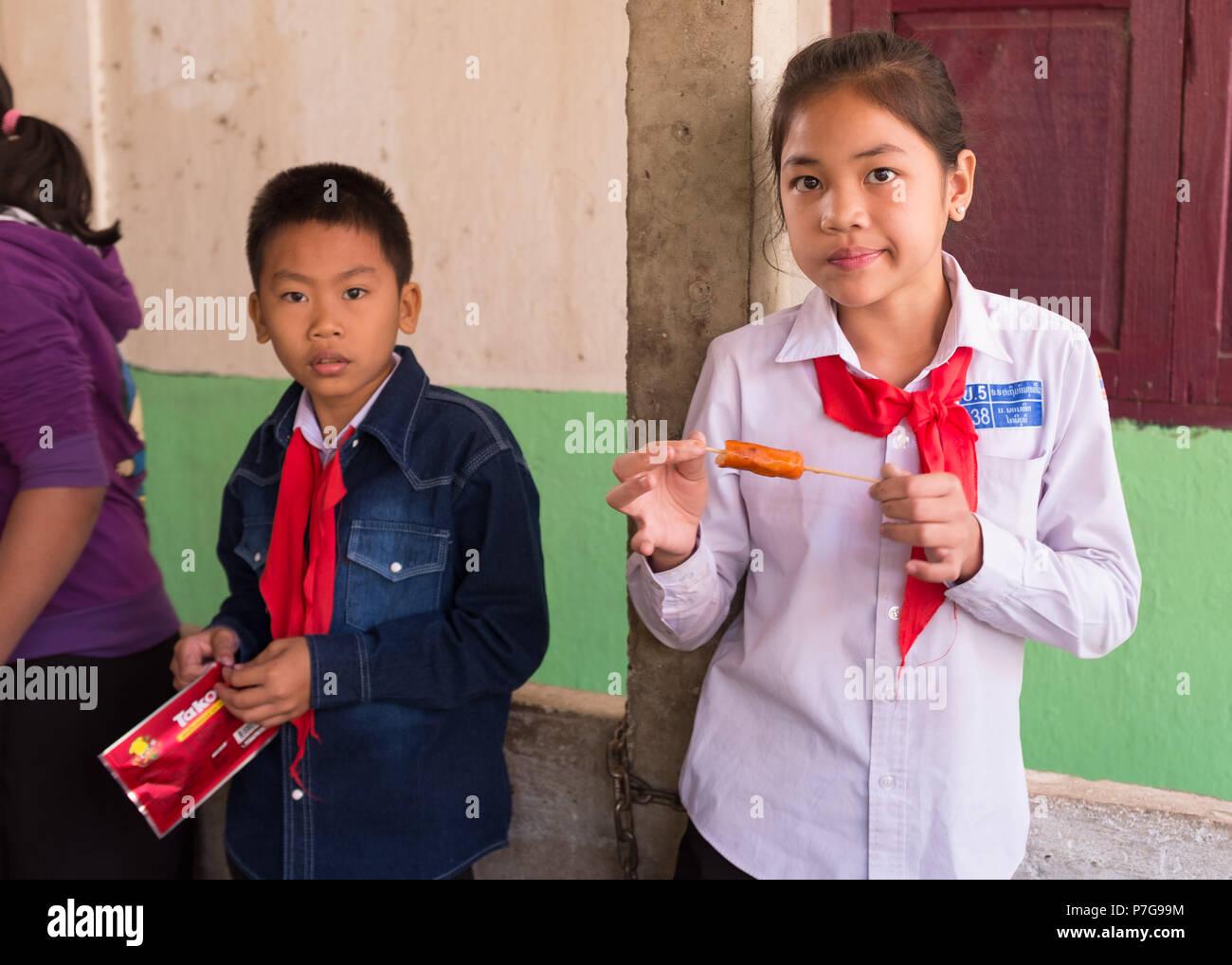 Portrait of schoolchildren eating during lunch break at school, Vientiane, Laos, Asia. - Stock Image