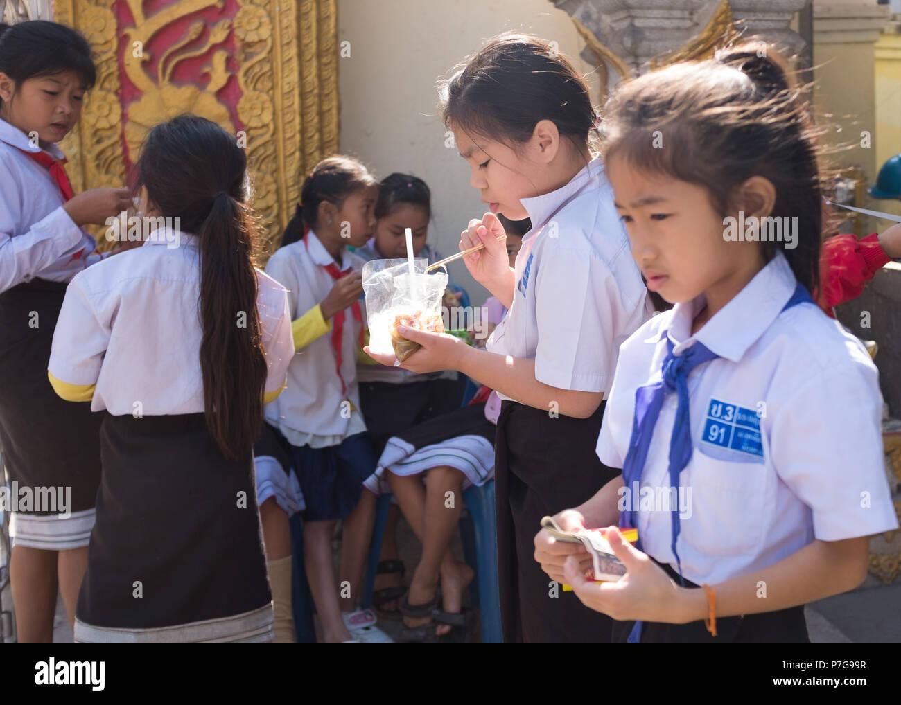 Schoolchildren eating during lunch break, Vientiane, Laos, Asia. - Stock Image