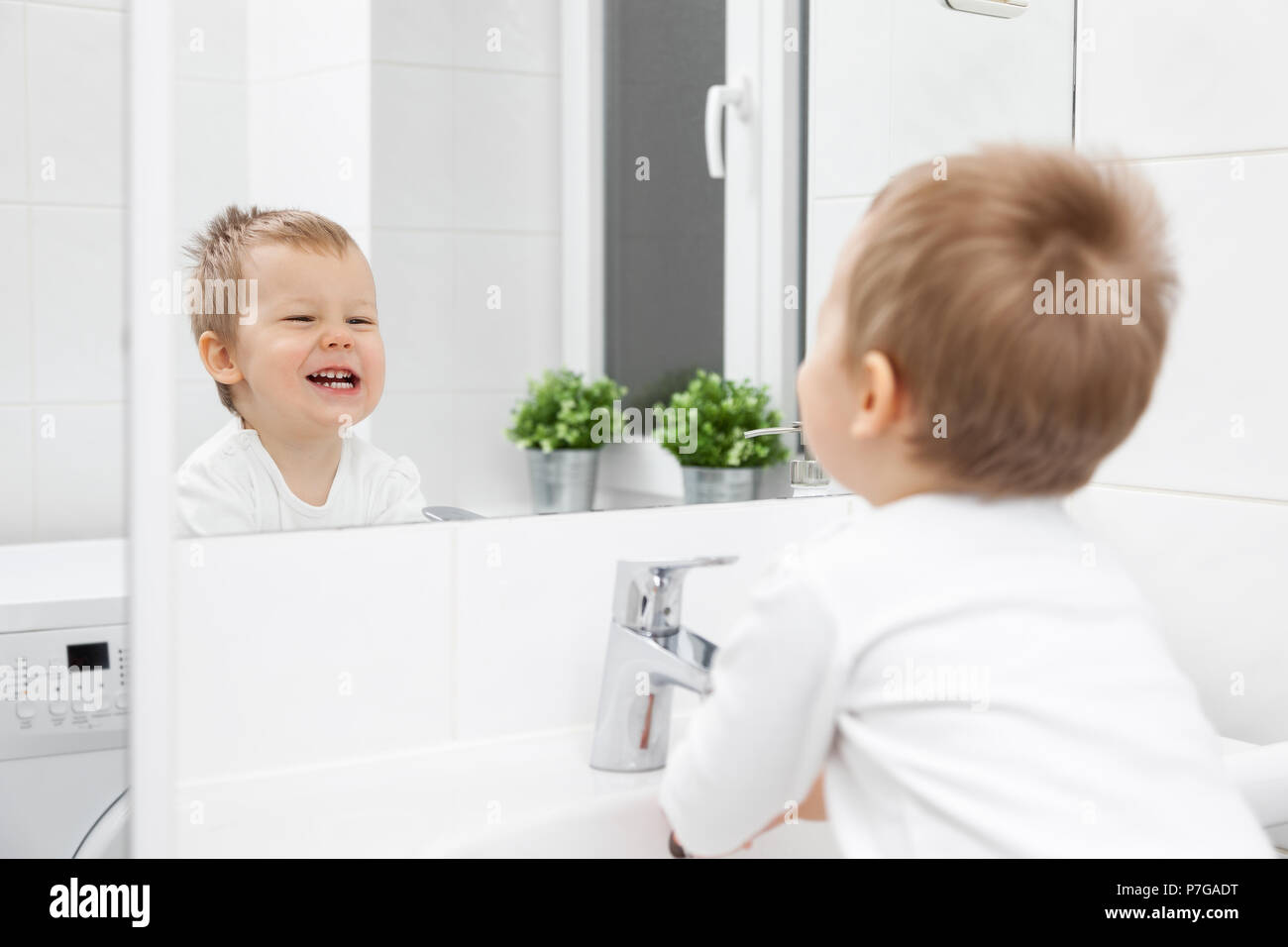 Cute toddler in the bathroom mirror learning how to wash his face - Stock Image