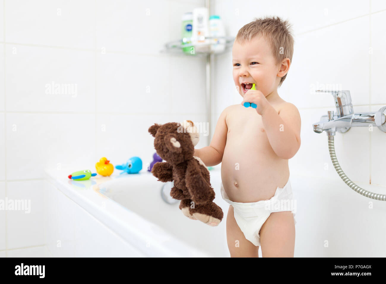 Adorable child learing how to brush his teeth in the bathroom - Stock Image