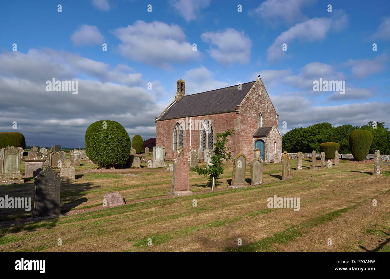 End on  view of the Parish Church of Stracathro with its surrounding well tended Graveyard enclosed by a Drystone Wall. Stracathro, Angus, Scotland. - Stock Image