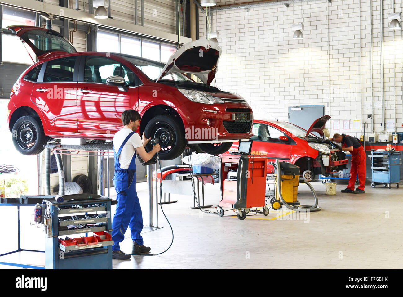 tyre change on the car by mechanics in a workshop - Stock Image