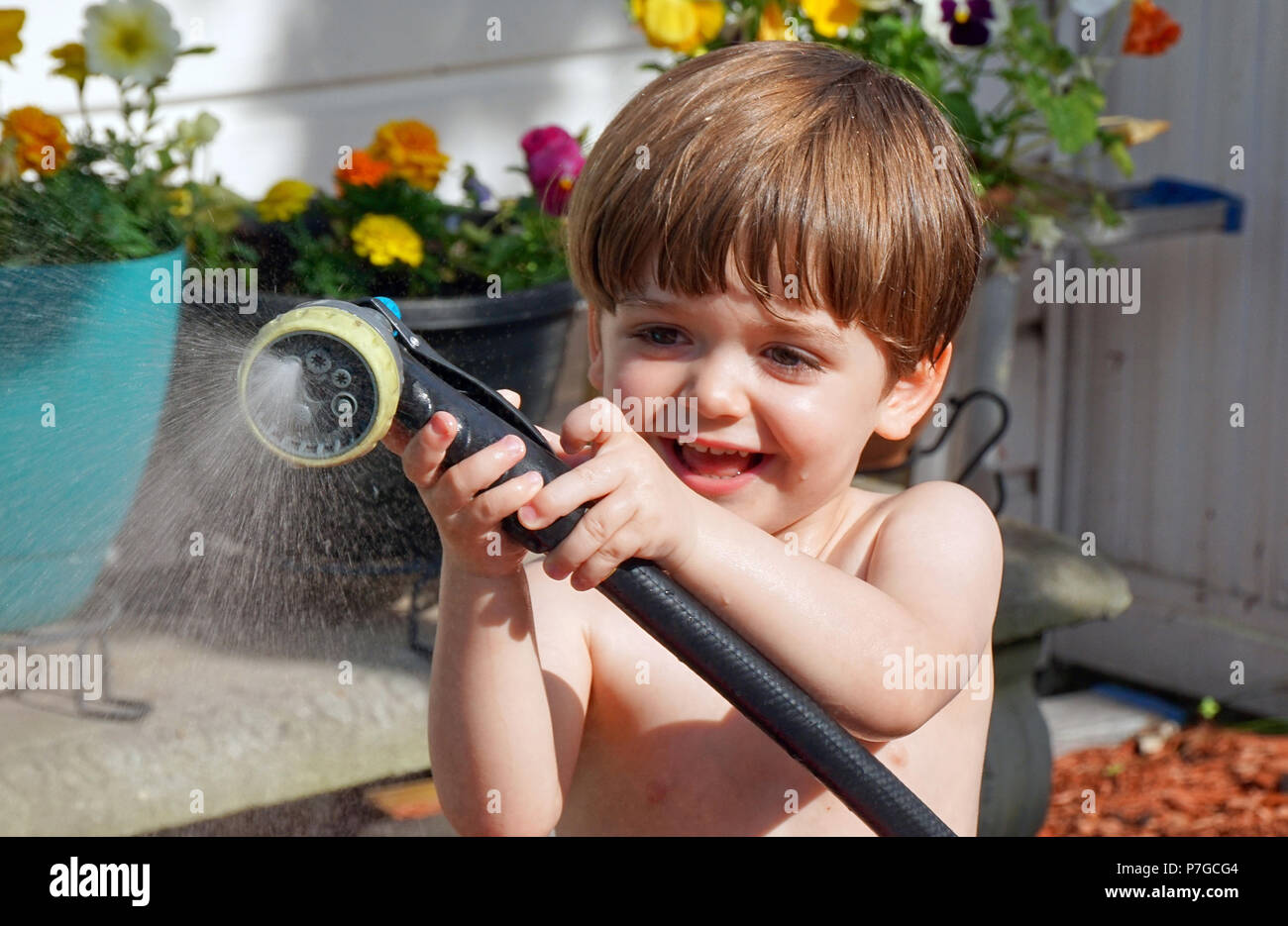 Montreal, Canada, July 2, 2018.Young three-old boy having fun with a garden hose during a heat wave.Credit Mario Beauregard/Alamy Live News - Stock Image