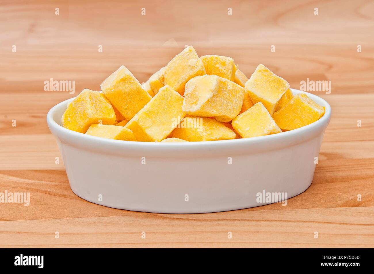 Cut of mango cut to cubes isolated on a plate on wooden background Stock Photo
