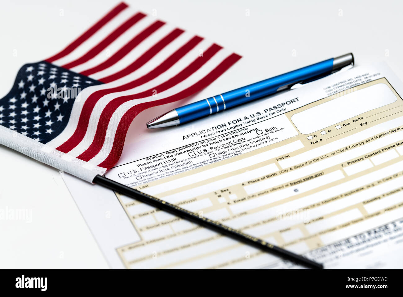 Fairfax, USA - April 11, 2018: U.S. Department of State application for US, American passport on table with pen, flag - Stock Image