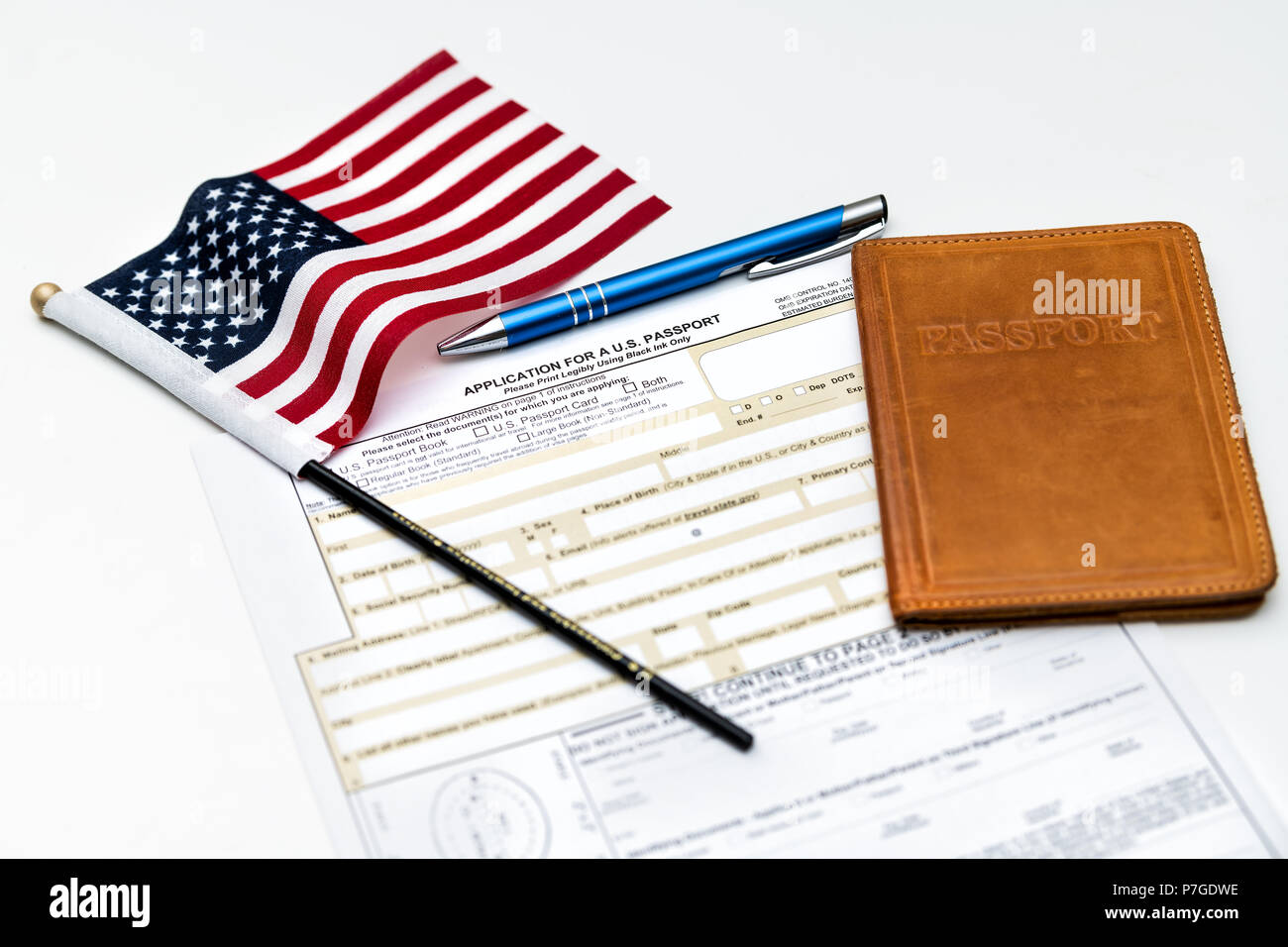Fairfax, USA - April 11, 2018: U.S. Department of State application for US, American passport on table with pen, flag and passport case, cover - Stock Image